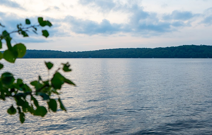 A beautiful view of North Twin Lake during summer twilight. The lake is calm, and we see the leaves of a tree in the left foreground.