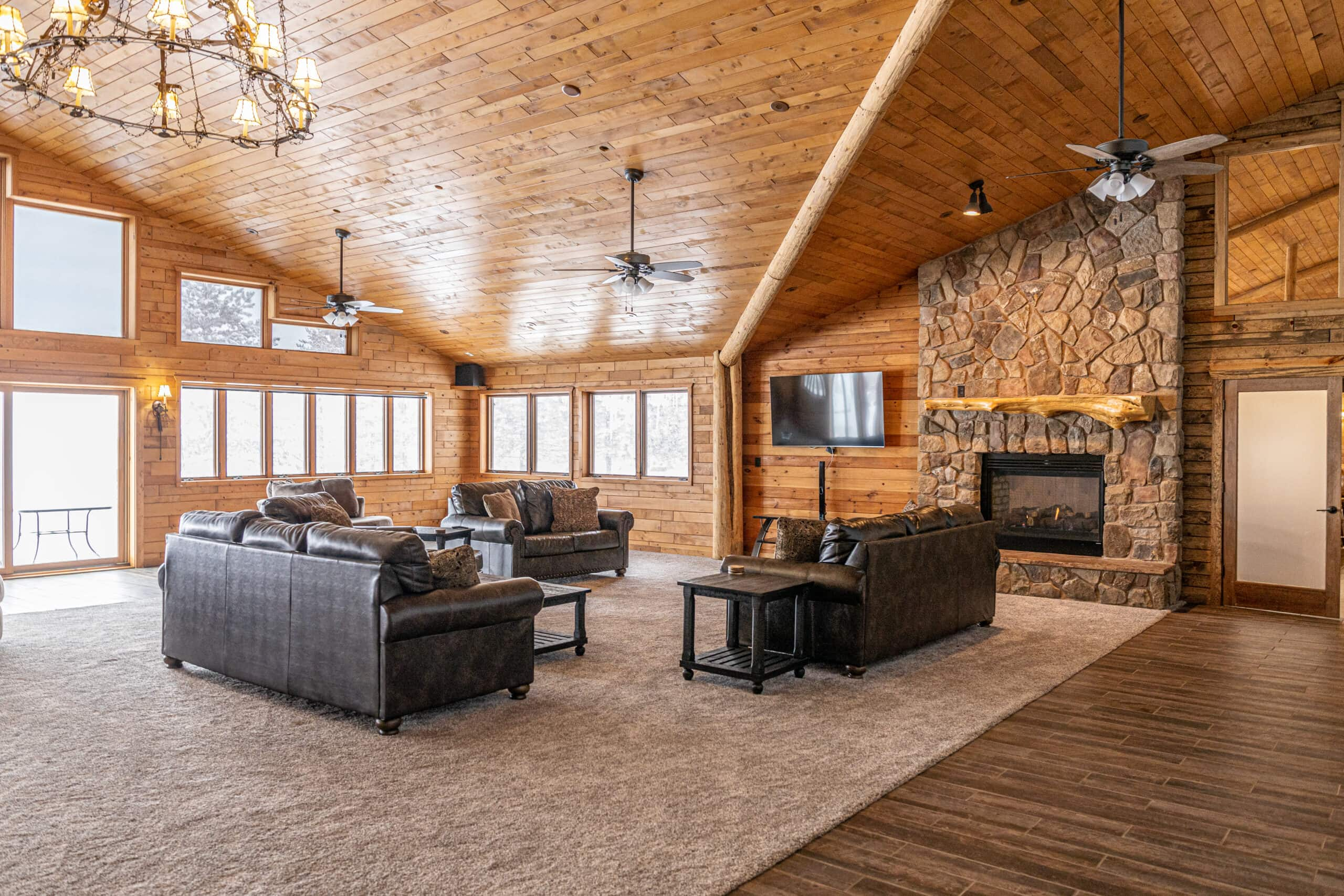 The great room at Holiday House lodge. Bright winter sunlight and a lake view are visible through banks of windows. Rustic wood paneling and warm lighting give the room a homey feel. To the right is a massive stone fireplace with a mantle made from a varnished log. At center is a carpeted conversation area with modern leather furniture, Rustic style black end tables and coffee tables, and 3 ceiling fans for perfect temperature control.